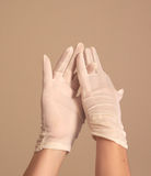 Woman modeling and adjusting vintage formal white gloves Stock Photography