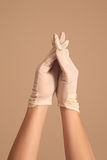 Woman modeling on vintage white gloves with fingers crossed Royalty Free Stock Photography