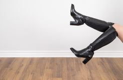 Woman Modelling Black Knee High Leather Boots  2. Woman Modelling Black Knee High Leather Boots Against a Grey Wall  1 Royalty Free Stock Photo