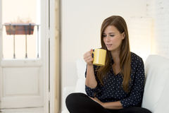 Woman at modern apartment  living room home couch enjoying coffee tea cup Royalty Free Stock Image