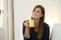 Woman at modern apartment  living room home couch enjoying coffee tea cup Royalty Free Stock Images