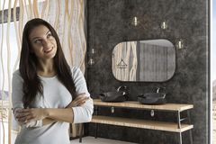 Woman in modern bathroom with loft mirror. Dreaming woman in modern loft bathroom with balck faucets and concept mirror royalty free stock photo