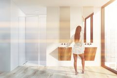 Woman in modern bathroom with shower and sink. Young woman in nightgown standing in modern bathroom with white walls, wooden floor, two wooden sinks and shower royalty free stock photography