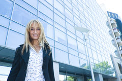 Woman By A Modern Building. Smiling young blond woman standing outdoors near a multi-story modern design building Stock Images