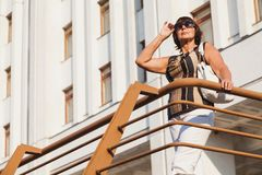 Adult woman stands in front of modern building. Woman in a modern city. A cute elderly leans on a railing in front of a tall white building on a hot summer day stock image