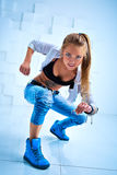 Woman modern dancer. Young woman modern dancer with tattoo on body in bright white and blue interior royalty free stock images