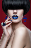 Woman with modern haircut with blue lips. And earrings stock image