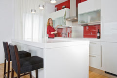 Woman in modern kitchen Royalty Free Stock Image