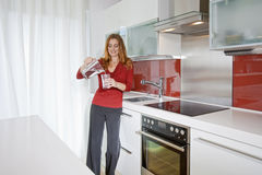 Woman in modern kitchen Stock Images