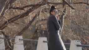 Woman modèle urbain en manteau et verres de mode ayant l'amusement Fille sexy de hippie de charme, coiffure à la mode dans des ru banque de vidéos