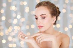 Woman with moisturizing cream on hand over lights stock photo