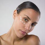 Woman with moisturizing lotion on face. A studio closup of a beautiful young woman with many littles spots of moisturizing lotion on face Royalty Free Stock Photo