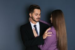 Woman molesting her male colleague on dark background. Sexual harassment at work stock photography