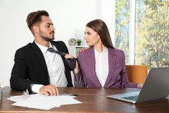 Woman molesting her male colleague in office. Sexual harassment at work royalty free stock image
