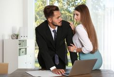 Woman molesting her male colleague in office. Sexual harassment at work royalty free stock images