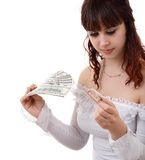 Woman with money. Young brown-haired woman thinking how to spend her money Stock Image