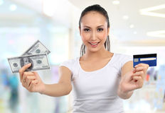 Woman with money and credit card. Woman showing  money and credit card in shopping mall Royalty Free Stock Photo