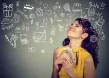 Woman with money dreaming how to spend it all. Young woman with money dreaming how to spend it all Royalty Free Stock Images