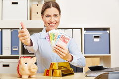 Woman with money and gold holding thumbs up. Smiling successful woman with money and gold holding her thumbs up stock images