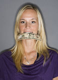 Woman with money in her mouth Stock Photo