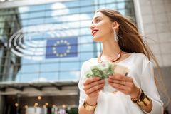 Woman with money near the parliament building in Brussel. Woman holding euro banknotes in front of the Parliament building of European Union in Brussel city stock image