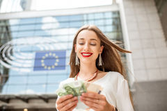 Woman with money near the parliament building in Brussel Royalty Free Stock Images