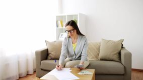 Woman with money, papers and calculator at home stock footage