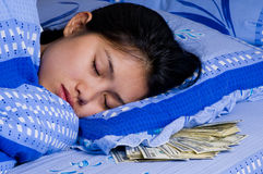 Woman with money under her pillow Royalty Free Stock Images