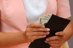Woman With Money and a Wallet. Woman in Pink is Taking Out Money From a Wallet royalty free stock photo