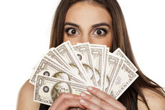 Woman and money. Young woman peeking behind the stack of money in her hands Royalty Free Stock Photography