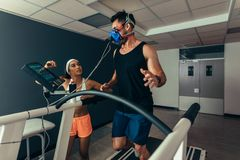Woman monitoring runner with mask on treadmill royalty free stock images