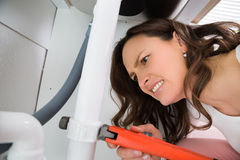 Woman With Monkey Wrench Tightening Pipe. Close-up Of Woman With Monkey Wrench Tightening White Pipe royalty free stock photo