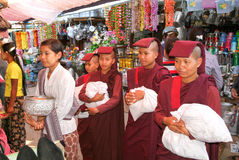 Woman with monks asking for offers at the market of Pyin U Lwin Royalty Free Stock Photo