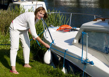 Woman mooring boat on the river Royalty Free Stock Image