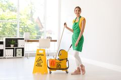 Woman with mop and bucket cleaning office. Young woman with mop and bucket cleaning office royalty free stock photos
