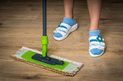 Woman with mop mopping wooden laminate floor. At home Royalty Free Stock Photography