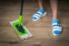 Woman with mop mopping wooden laminate floor. At home Royalty Free Stock Photos