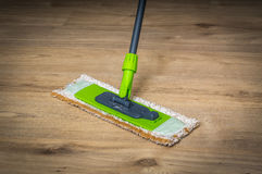 Woman with mop mopping wooden laminate floor. At home Royalty Free Stock Images