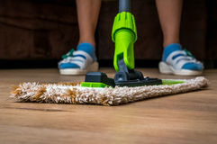 Woman with mop mopping wooden laminate floor. At home Stock Images