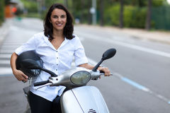 Woman on a moped. Woman siting on a moped on a street with helmet in hand Royalty Free Stock Photos