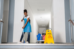 Woman Mopping Corridor. African Woman Mopping Corridor Besides Caution Sign Royalty Free Stock Images
