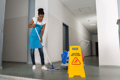 Woman Mopping Corridor. African Woman Mopping Corridor Besides Caution Sign Royalty Free Stock Photos