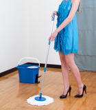 Woman mopping the floor. A woman in beautiful dress mopping the floor royalty free stock photos