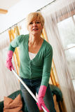 Woman mopping the floor in her home. Woman cleaning and mopping the floor in her home Royalty Free Stock Photos