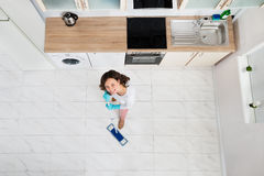 Woman Mopping Floor. High Angle View Of Woman Mopping Floor In Kitchen Stock Image