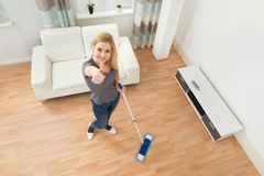 Woman Mopping Floor. High Angle View Of Young Woman Mopping Floor At Home Royalty Free Stock Images
