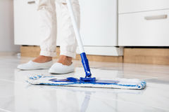 Woman Mopping The Floor In Kitchen. Cleaning Service Woman Mopping The Floor In Kitchen At Home Royalty Free Stock Image