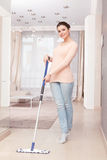 Woman mopping floor in living room Stock Photography