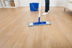 Woman mopping hardwood floor at home Royalty Free Stock Photos