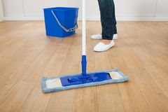Woman mopping hardwood floor at home Royalty Free Stock Photography